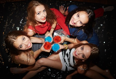 cheers: Group of pretty girls with martini looking at camera at party