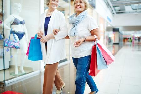 spending money: Mature females spending money on shopping