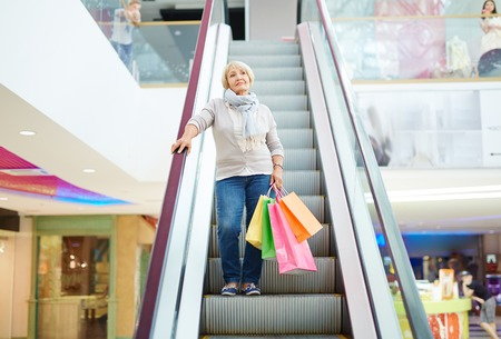 paperbags: Aged consumer with paperbags standing on stairs of escalator in shopping mall Stock Photo