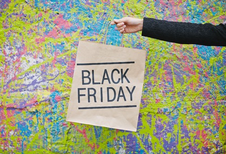 shoppingbag: Stretched human hand holding Black Friday paperbag