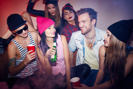 young friends: Stylish men and women enjoying raging swag party, talking and laughing on sofas with beer in crowded smoky room