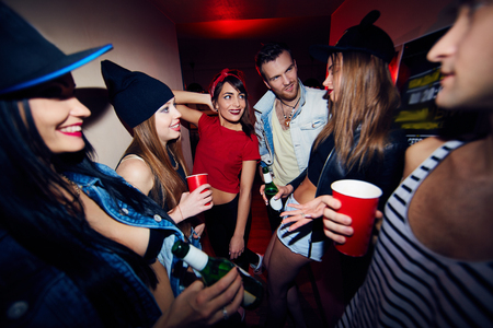 get dressed: Company of young girls and guys dressed to latest trend leaving noisy party to get some fresh air, they stand in dim club corridor laughing, talking and drinking beer