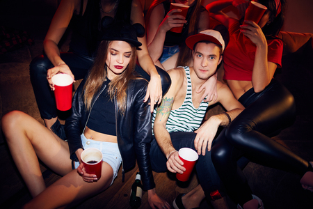after party: Beutiful sexy girl and stylish guy sitting on floor in dark crowded room at swag party among other people, mess and chaos of bottles and cups Stock Photo