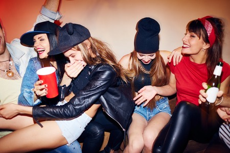 Group of several young people getting drunk at underground swag party, one girl  almost choking on beer as all suddenly burst out laughing when chilling out on couch in quiet corner of crowded nightclub Stock Photo
