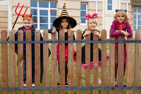 repent: Children in traditional Halloween attire standing along fence outdoors