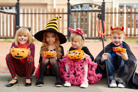 Row of kids with pumpkin bowls full of candies looking at camera