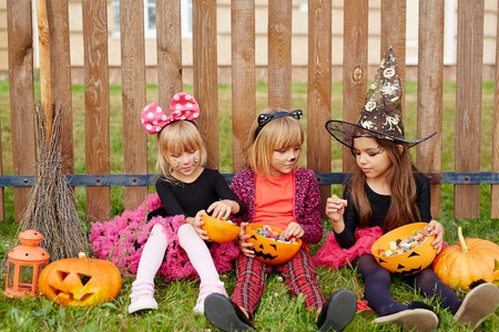 Three cute witches sitting on grass with Halloween candies