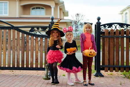 Halloween girls with treats standing along wooden fence