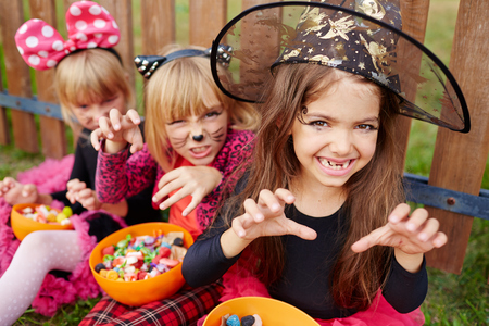 Halloween girl in witch hat showing frightening gesture