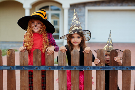 Girls in witch hats standing by fence on Halloween day