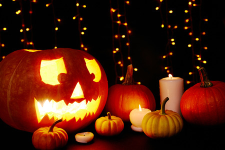 cucurbit: Halloween composition lit by burning candles and garlands