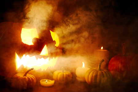 repent: Scary jack-o-lantern surrounded by burning candles in the dark