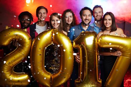 Happy friendly people enjoying new year party Stock Photo