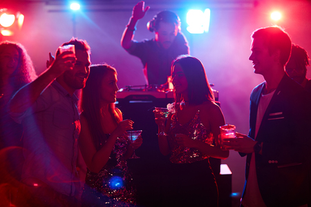 clubber: Friends with cocktails talking at night party in disco club