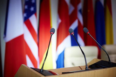 debating: Empty tribune with microphones in congress hall Stock Photo