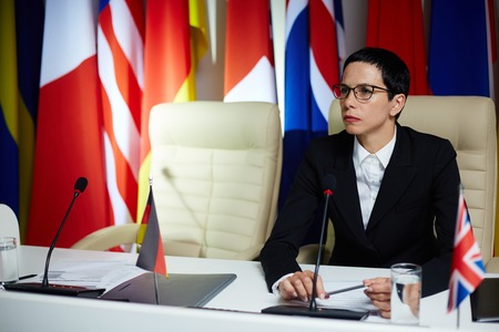 Female politician listening to spokesperson during summit Stock Photo