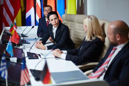 delegar: delegado serio escuchar a algún conocido en la cumbre Foto de archivo