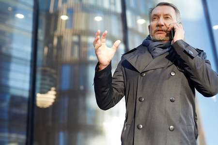 Mature man in trenchcoat speaking on cellphone in urban environment