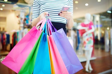 Modern shopper writing sms in trade center