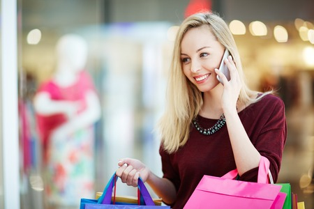 Young blond woman talking on mobile phone after shopping