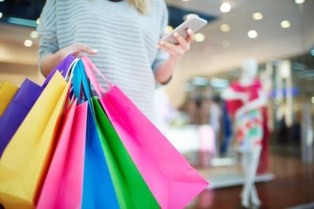Paperbags in handen van mobiele shopaholic met smartphone