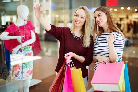 shopwindow: Two smiling shoppers making selfie by shop-window