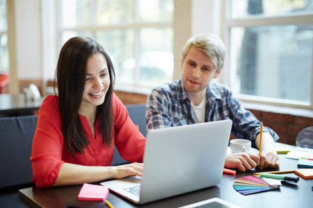 artistic addiction: Pretty student of design faculty networking with her groupmate near by Stock Photo