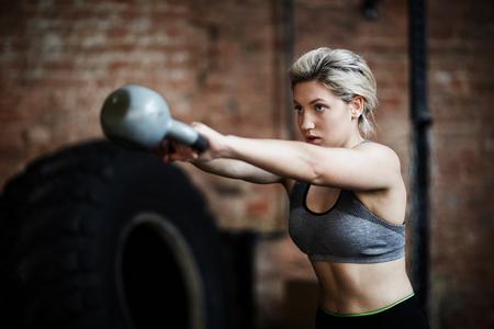 kettles: Mujer joven que hace ejercicio físico con la campana hervidor