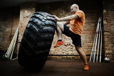 Sportivo facendo fatica, mentre lanciando pneumatico durante l'allenamento