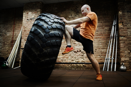 tire: Sportsman making effort while flipping tire during workout