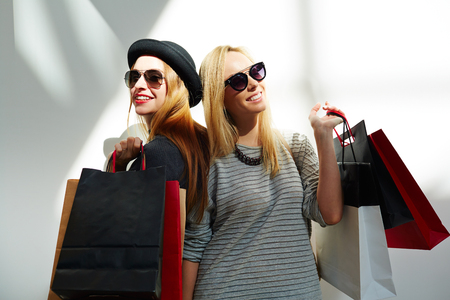 Stylish women in sunglasses holding paperbags