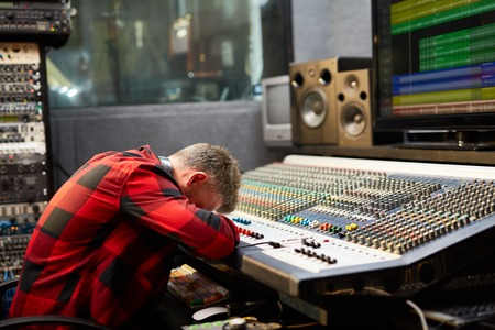 soundboard: Tired deejay putting his face on soundboard in audio studio Stock Photo