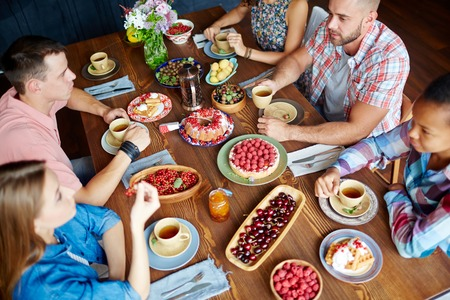 Amici che celebrano giorno del Ringraziamento da tavolo servito