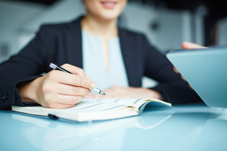 hand pen: Secretary with pen holding it over open notebook Stock Photo