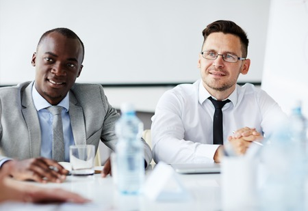 Two confident men sitting at business conference Stock Photo