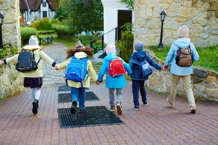 schoolkids: Happy schoolkids running to school