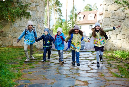 schoolkids: Group of ecstatic schoolkids hurrying to school Stock Photo