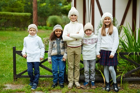 Cute kids in knitted caps and sweaters looking at camera