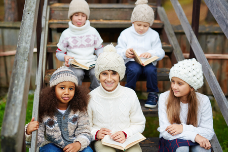 Clever children reading books outdoors Stock Photo