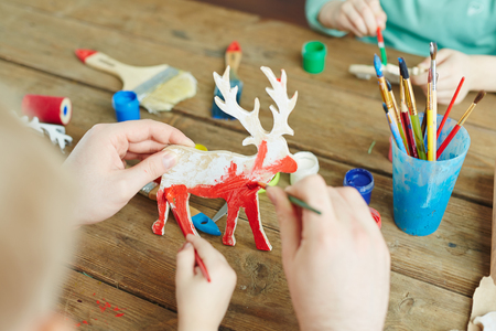 artwork: Hands of adult and kid painting wooden deer in red