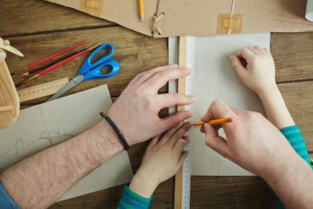 crayon  scissors: Man and his son making sketch of toy plane Stock Photo