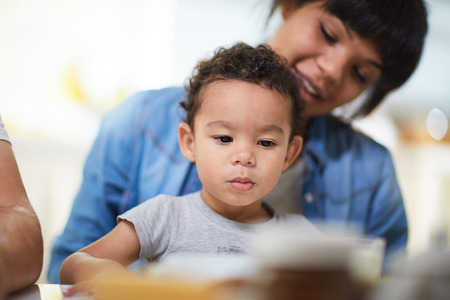 Nettes Kind auf den Hintergrund seiner Mutter