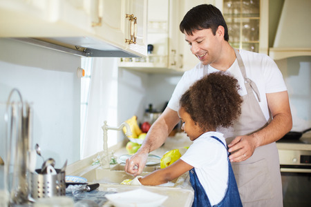 foster: Little girl washing dishes with her father near by