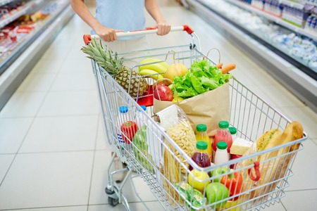 Consumer cart with various food products being pushed by woman
