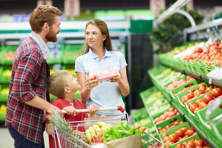Young buyer looking at her husband while choosing tomatoes in grocery store Stok Fotoğraf
