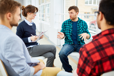 Circle of students practicing psychological therapy in group Stock Photo