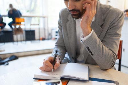 persona escribiendo: El hombre escrito en el cuaderno mientras habla por el teléfono celular en el trabajo