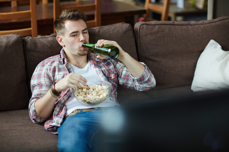 laze: Lazy young man drinking beer and eating popcorn in front of tv set