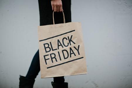 paperbag: Shopaholic carrying black friday paperbag Stock Photo