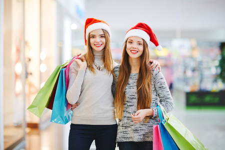 paperbags: Young women with paperbags visiting Christmas sale